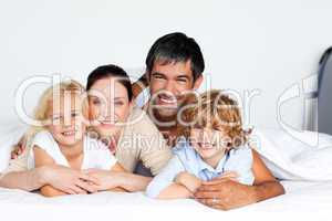 Smiling family together on bed