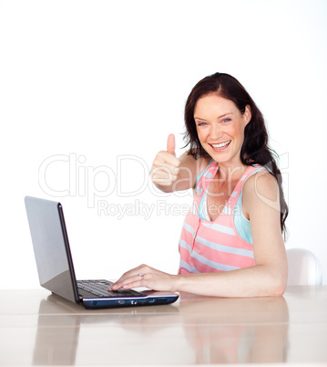 Happy woman having fun with laptop and thumb up