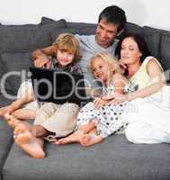 Family on a sofa with laptop