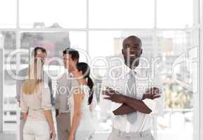 Young African - American Business leader standing inf front of business team smiling