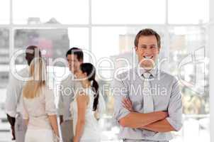 Attracive and confident business man in front of a group of associates smiling