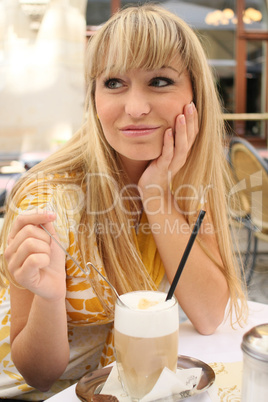 young blonde in a cafe with latte macchiato