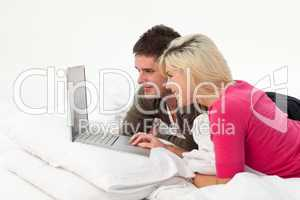 Boy using a latop in bed with his girlfriend
