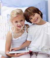 Happy brother and sister reading a book in bedroom
