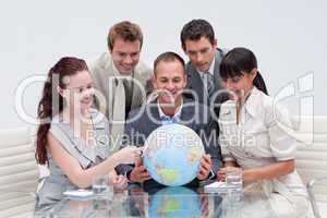 Business team holding a terrestrial globe. International busines
