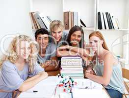 Smiling teenagers studying Science in a library