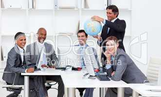 Smiling manager holding a globe with his team working at compute