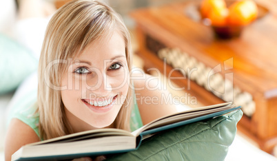 Happy woman lying on a sofa reading a book