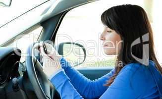 Attractive teen girl using a mobile phone while driving