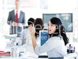 Portrait of a interrested businesswoman raising her hand
