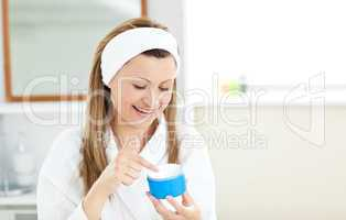 Radiant woman putting cream on her face wearing a headband in th