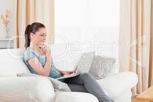 Beautiful woman relaxing with her laptop while sitting on a sofa