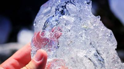 Hands in Close Up Examining Glacial Ice