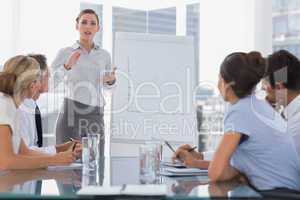 Businesswoman giving explication in front of a growing chart