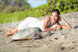 Turtle and woman lying on beach, Big Island Hawaii
