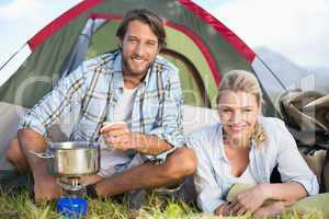 Attractive happy couple cooking on camping stove
