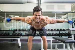 Smiling shirtless bodybuilder with arms outstretched in gym