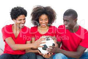 Football fans in red holding ball together