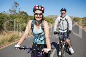 Fit happy couple going for a bike ride in the countryside