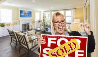 Young Woman Holding Sold Sign and Keys Inside Living Room