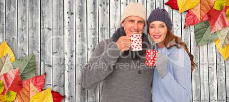 Composite image of happy couple in warm clothing holding mugs