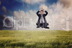 Composite image of businessman sitting in lotus pose with hands