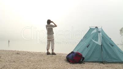 Frau mit Fernglas neben Zelt an See