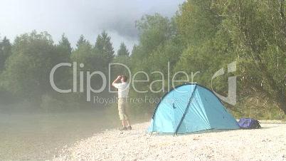 Mann mit Fernglas neben seinem Zelt in den Bergen