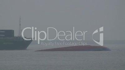 Schiff fährt an einem gekenterter Frachter vorbei 2