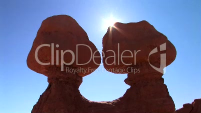 Sun peeks behind rock formations, time lapse