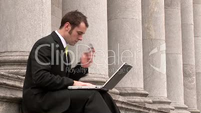 Business man Outdoors Using Laptop