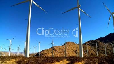 Rotierende Windräder vor bergiger Wüstenlandschaft