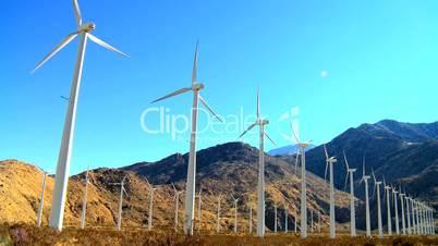 Windräder vor Bergen und Hügeln