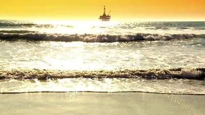 Ölplattform im Meer unter gelb/orangem Himmel