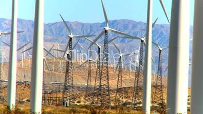 Rotierende Windkraftanlage vor bergiger Wüstenlandschaft