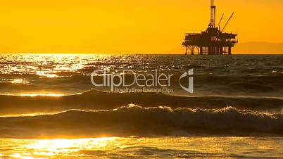Ölplattform im Meer unter orange/gelbem Himmel