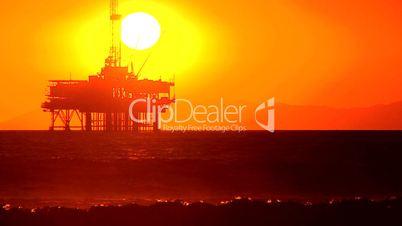 Ölplattform im Meer unter abendrotem Himmel mit Sonne