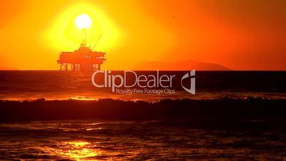 Bohrinsel im Meer unter abendrotem Himmel mit Sonne