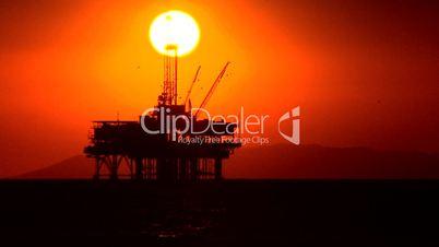 Ölplattform im Meer unter abendrotem Himmel