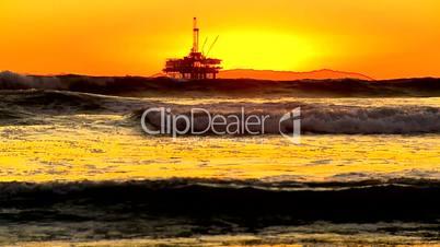 Bohrinsel im Meer unter orange/gelbem Himmel