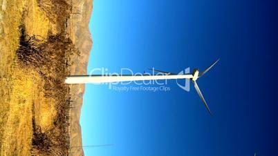 Rotierendes Windrad vor bergiger Wüstenlandschaft