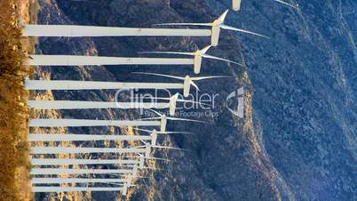 Eine Reihe rotierender Windräder vor bergiger Landschaft