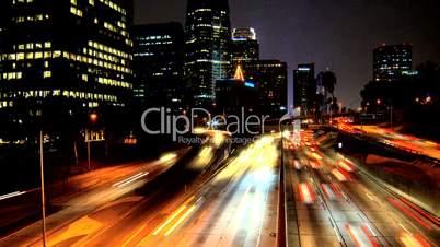 Schnell fließender Verkehr vor beleuchteter Skyline