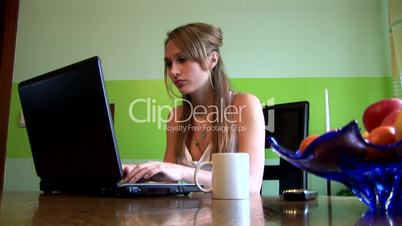 HD1080i Young girl working with laptop and drinkig coffee indoor