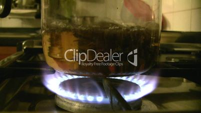 glass teapot is heated on a gas cooker.