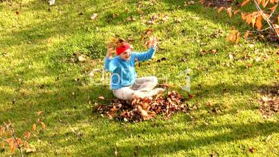 girl plays autumn leaves.