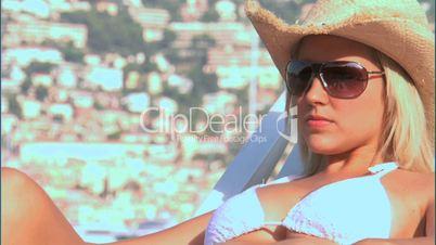 Blonde Frau im Bikini mit Sonnenbrille und Cowboyhut