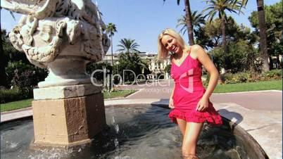 Blonde Frau planscht in einem Springbrunnen