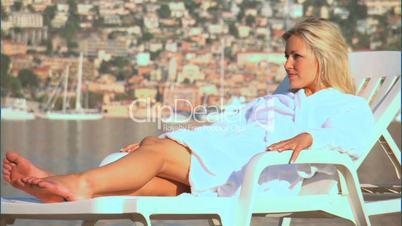 Blonde Frau entspannt im Liegestuhl