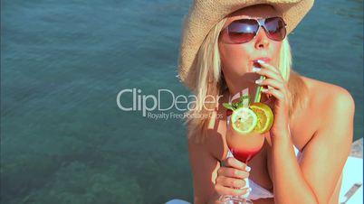 Blonde Frau trinkt einen Cocktail